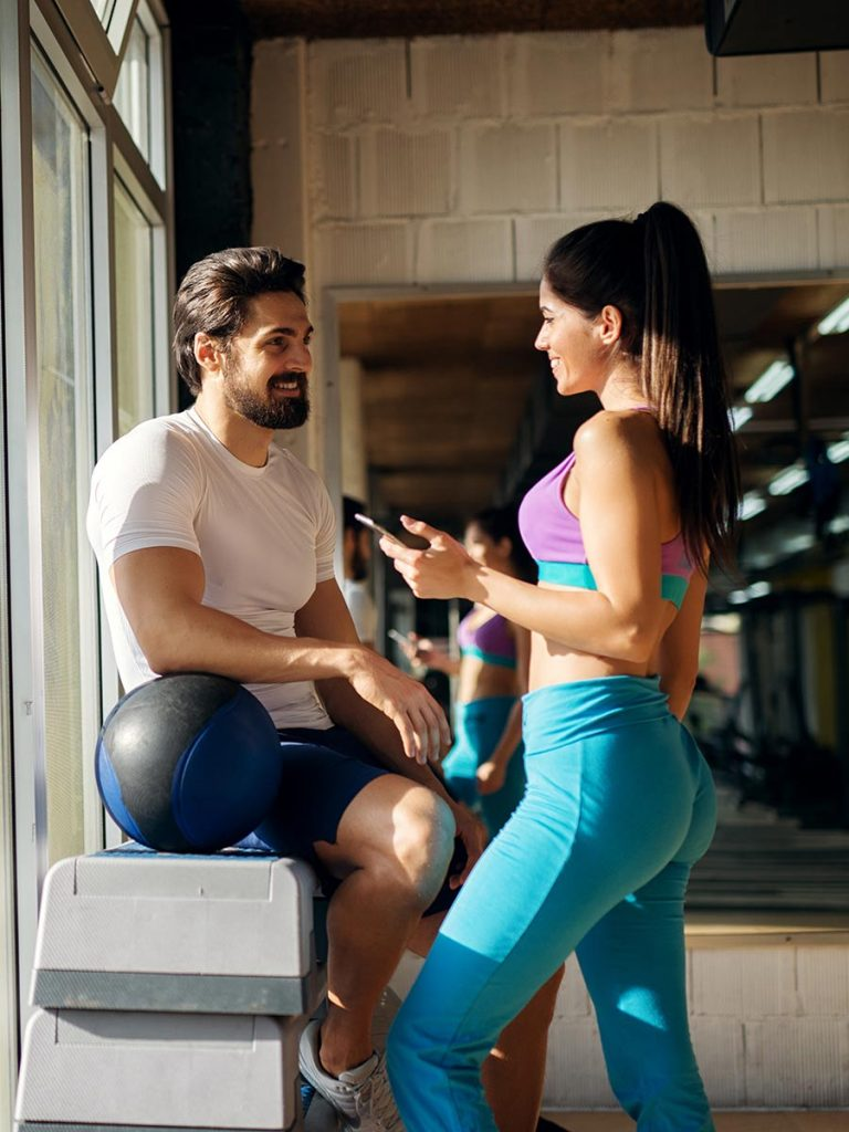 Man flirts with a woman at the gym