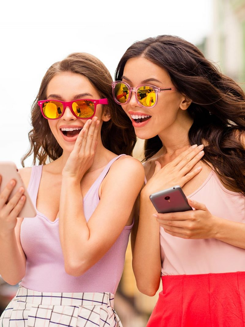Two pretty ladies chatting on their smartphones