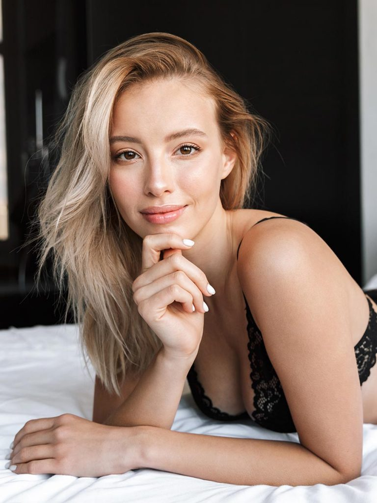 Blonde single woman alone in bed
