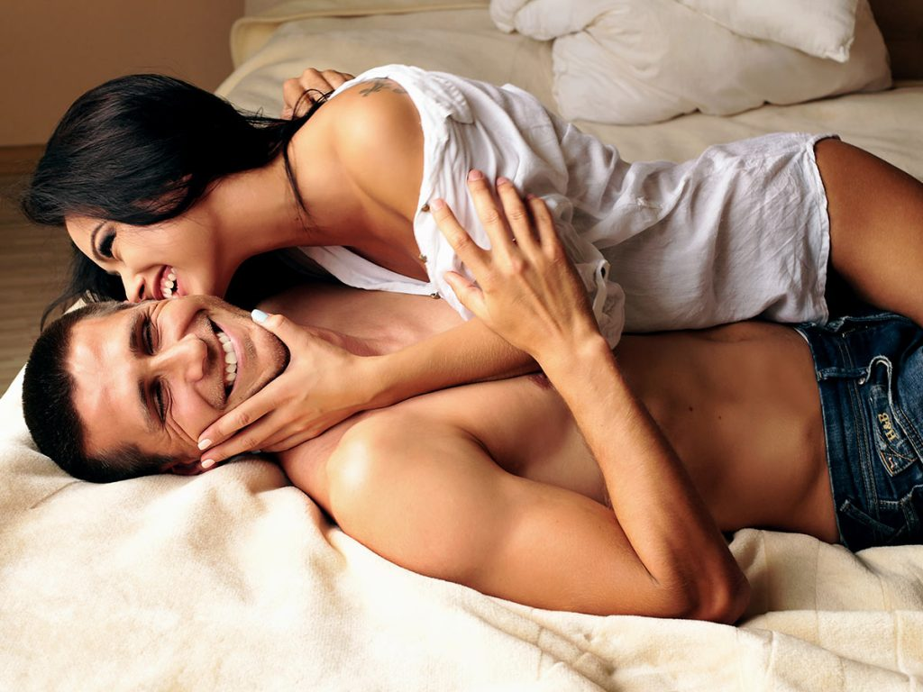 Attractive couple having fun in bed on a sensual date